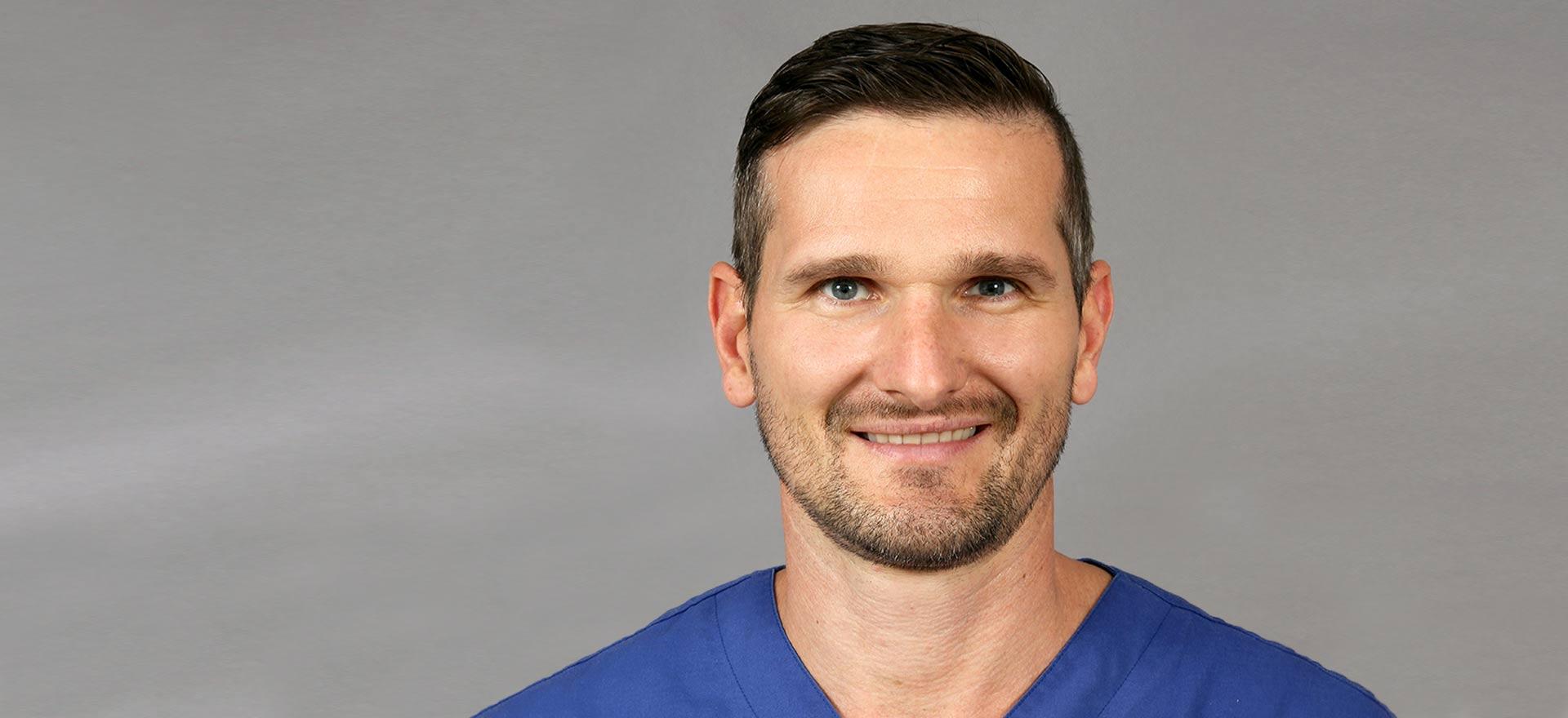 Zahnarzt Tobias Dieke aus Berlin lächelt freundlich in die Kamera.