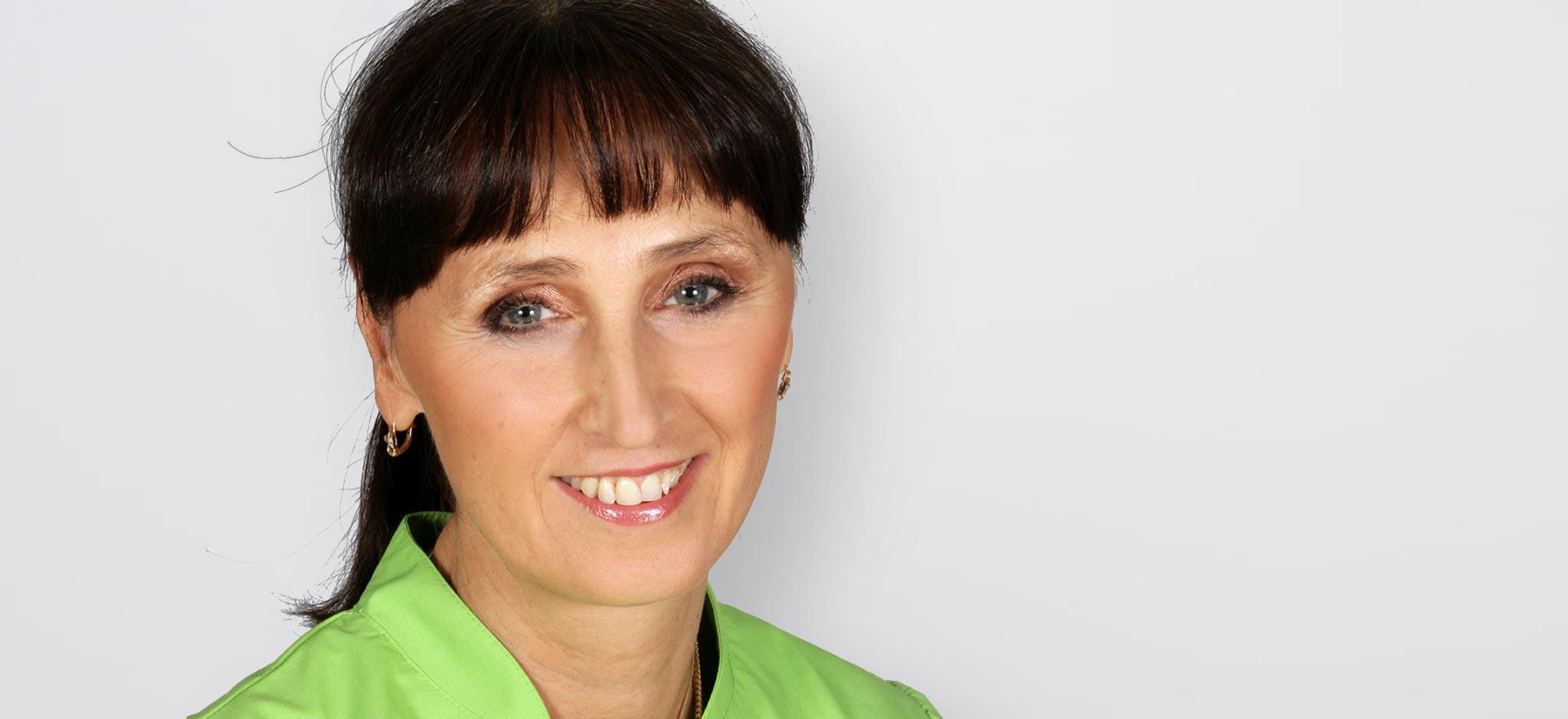 Zahnärztin Dr. Irina Brzenska lächelt in die Kamera.