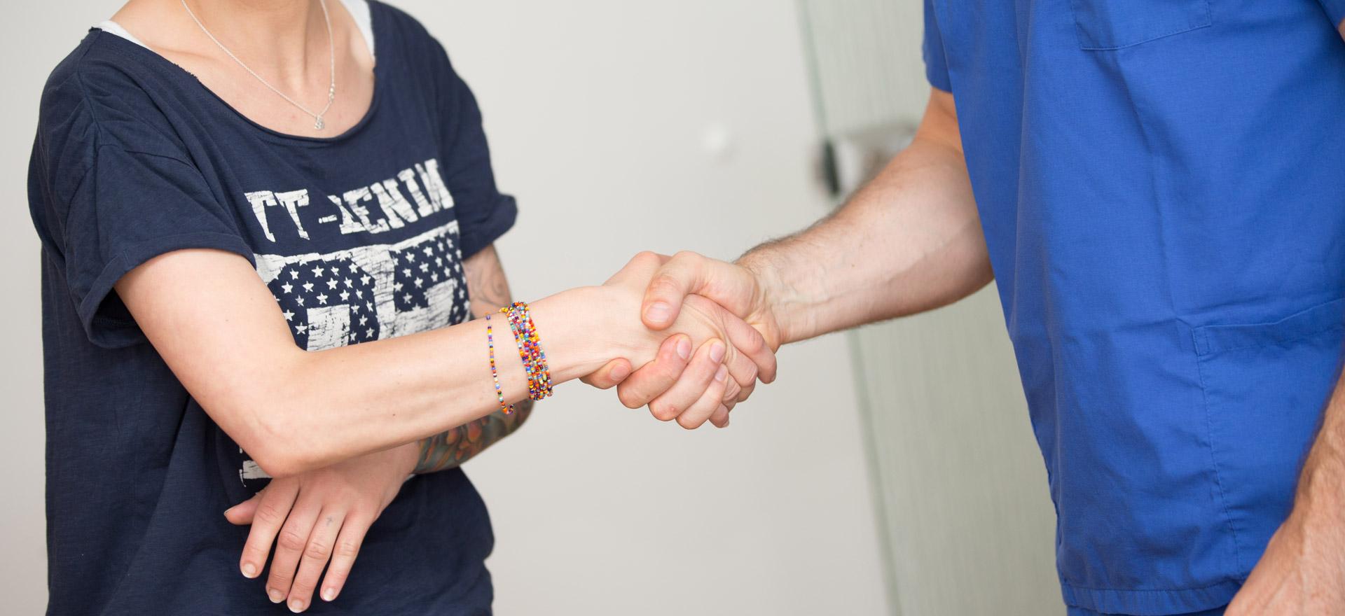 Zahnarzt und Patient schütteln sich die Hände für gute Partnerschaft.