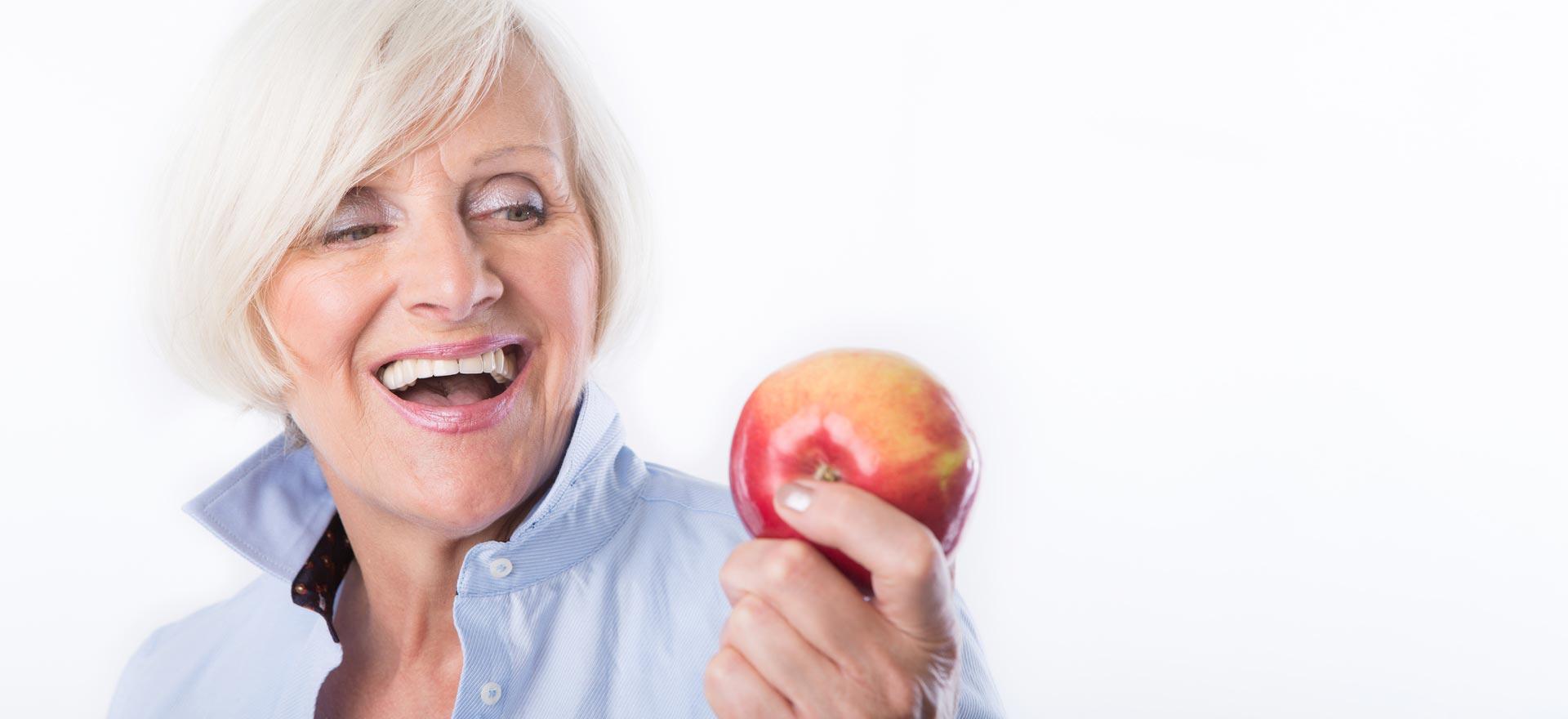 Ältere Frau beißt mit festen Zähnen auf Zahnimplantaten genussvoll in einen Apfel.