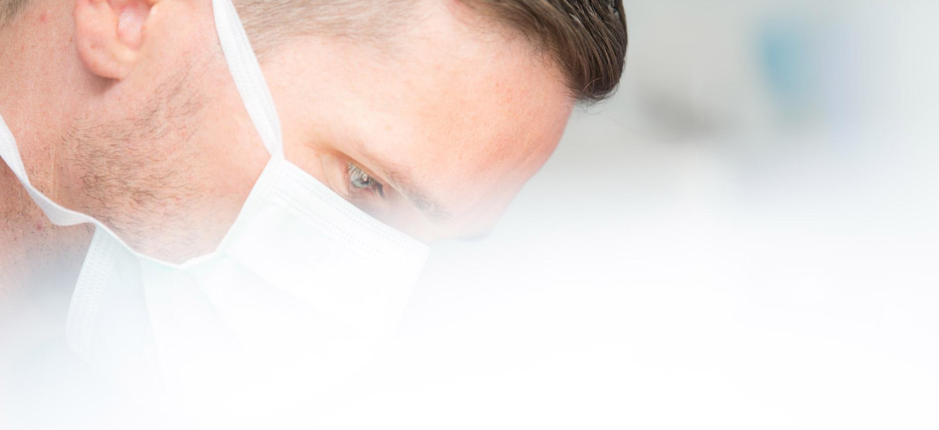 Zahnarzt Tobias Dieke trägt bei der OP einen Mundschutz.
