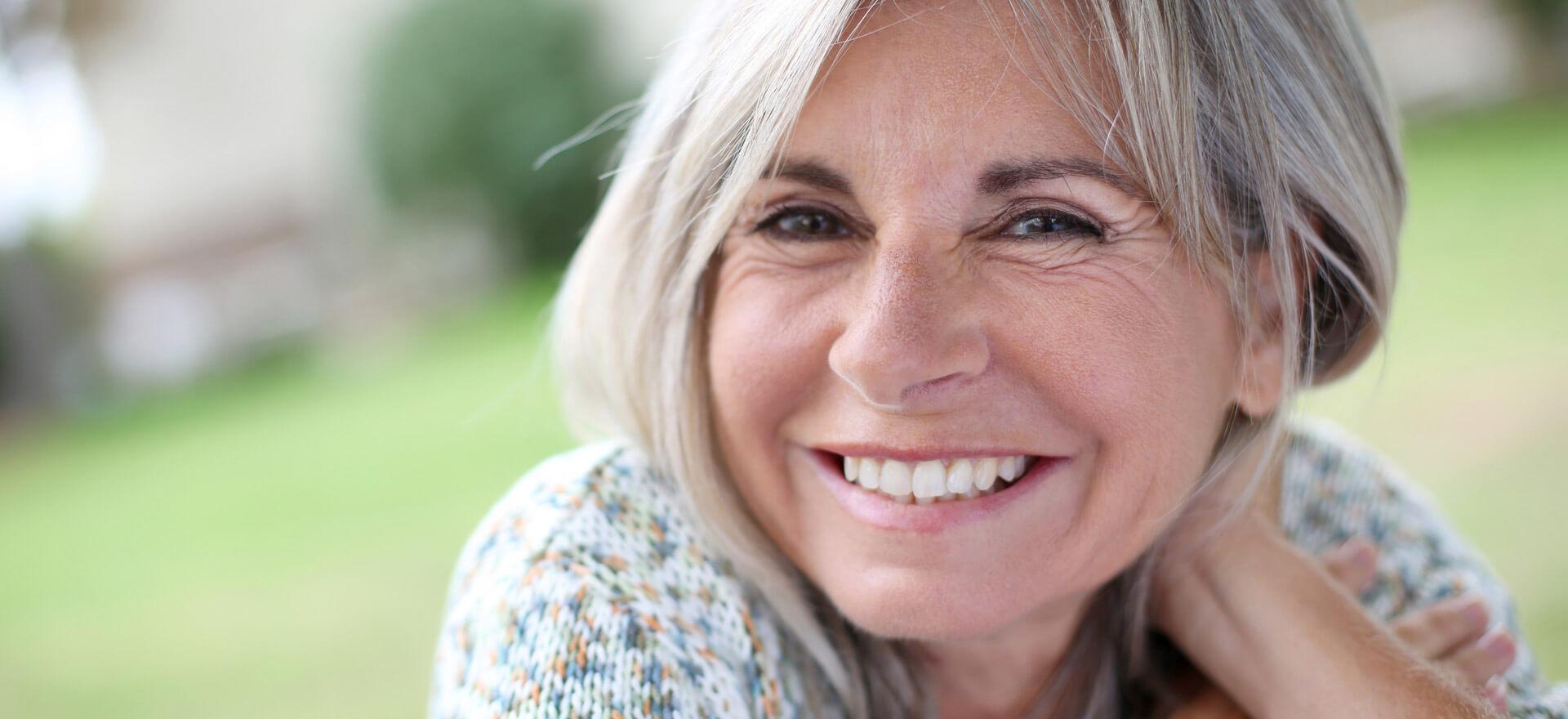 Reife Frau lächelt nach der Faltenbehandlung in Berlin wieder jung und schön.