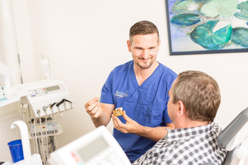 Zahnarzt Tobias Dieke erklärt Patienten, wie die Implantation in Berlin funktioniert.