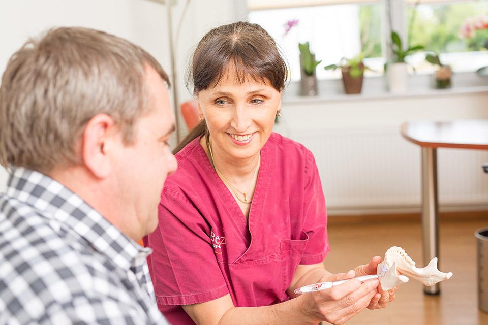 Dr. Dr. Irina Brzenska M.Sc. erklärt Patienten beste Stelle für Zahnimplantate setzen in Berlin.